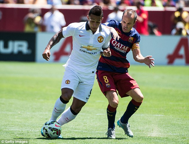 Barcelona's Andres Iniesta attempts a tackle on Manchester United's Memphis Depay on Saturday