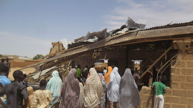 People gather around the Redeemed Christian Church of God after a woman suicide bomber killed five people in Potiskum Nigeria. It was the first in a string of attacks on Sunday that killed 44