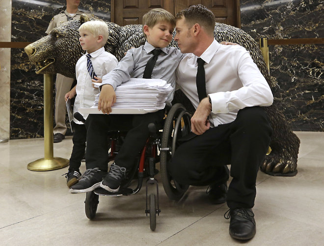 Otto Coleman 6 waits outside the Governor's office with his brother Fenton 4 left and father Joshua to deliver a stack of petitions with thousands of signatures calling on California Gov. Jerry Brown to veto a measure requiring nearly all California