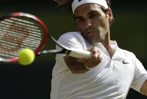 Roger Federer of Switzerland makes a return to Andy Murray of Britain during their men's singles semifinal match at the All England Lawn Tennis Championships in Wimbledon London Friday