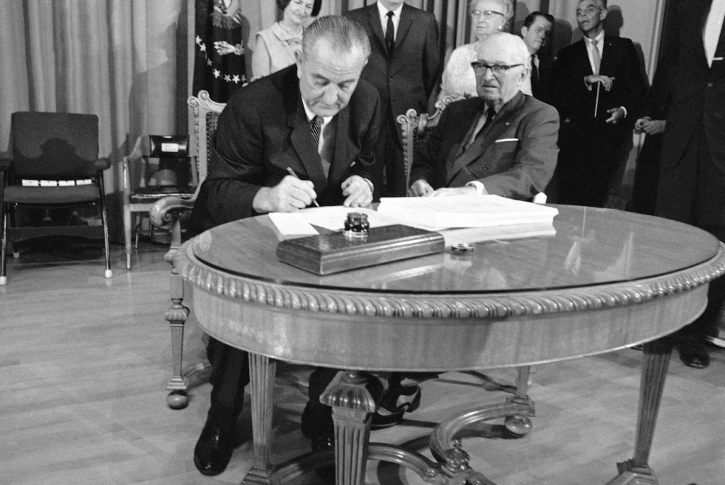 President Lyndon B. Johnson uses the last of many pens to complete the signing of the Medicare Bill into law at ceremonies at the Truman Library in Independence Missouri