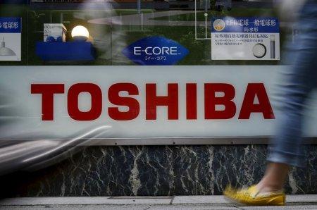 Pedestrians walk past a logo of Toshiba Corp outside an electronics retailer in Tokyo Japan
