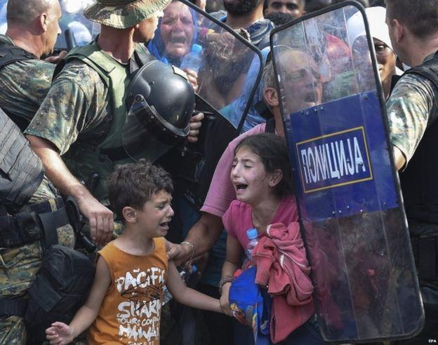 Desperation as 2000 migrants rush past Macedonian police at Greek