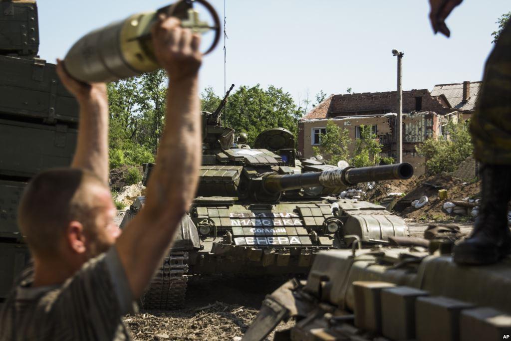 FILE- A pro Russia rebel loads shells onto a tank near Donetsk eastern Ukraine