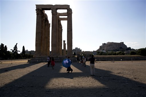 A woman carries a parasol for the strong afternoon sun as a group of tourists walk around the ruined ancient Temple of Olympian Zeus with the Acropolis hill in the background in central Athens on Wednesday Aug. 19 2015. Germany's parliament overwhelmi