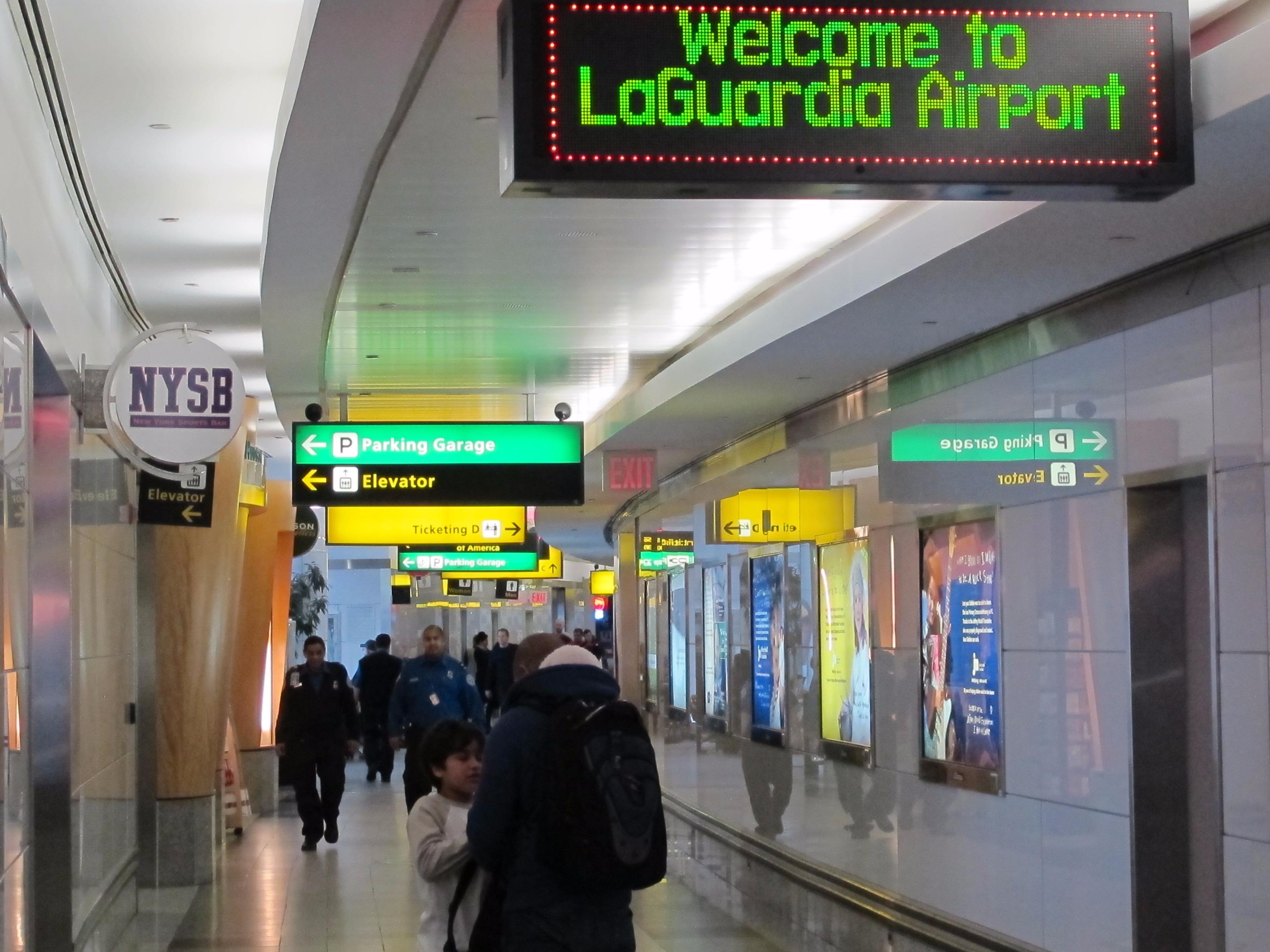 Passengers manoeuvre through cramped hallways at New York's La Guardia Airport