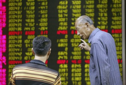 Investors talk in front of an electronic board showing stock information at a brokerage house in Beijing China