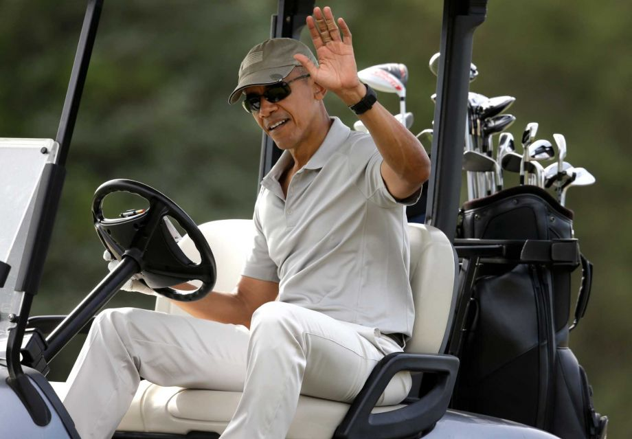 President Barack Obama waves to people from his golf cart while golfing Saturday Aug. 8 2015 at Farm Neck Golf Club in Oak Bluffs Mass. on the island of Martha's Vineyard. Obama is spending his first full day of vacation on the island playing golf