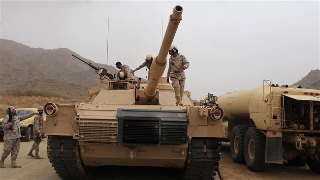 Saudi soldiers are seen on top of a tank deployed at the Saudi Yemeni border in Saudi Arabia's southwestern Jizan region