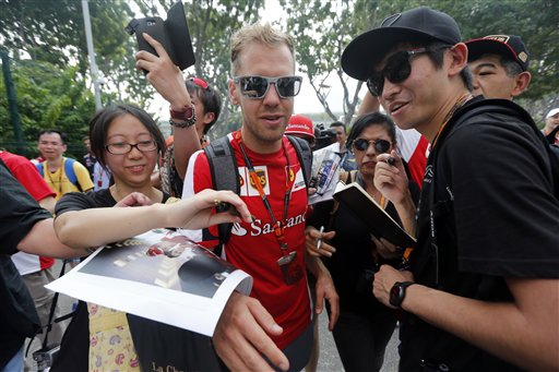 Ferrari driver Sebastian Vettel of Germany tries to get past fans as he arrives at the paddock ahead of the third practice session at the Singapore Formula One Grand Prix on the Marina Bay City Circuit in Singapore Saturday Sept. 19 2015.(AP