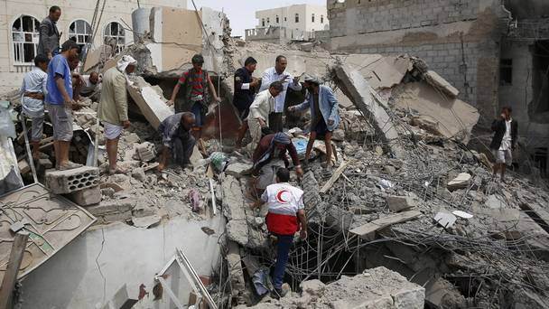 Rescue workers search for survivors after an air strike in Sanaa