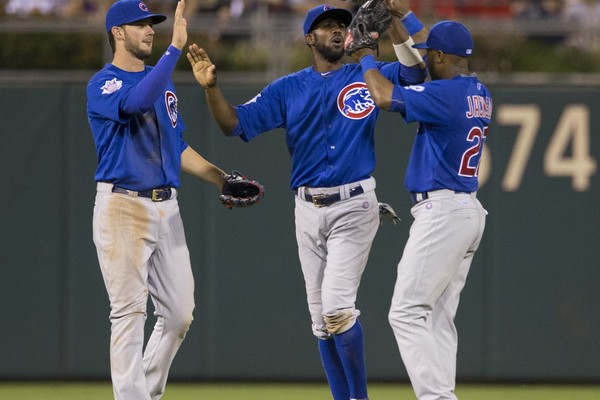 Kris Bryant #17 Dexter Fowler #24 and Austin Jackson #27 of the Chicago Cubs high five one another after the game against the Philadelphia Phillies