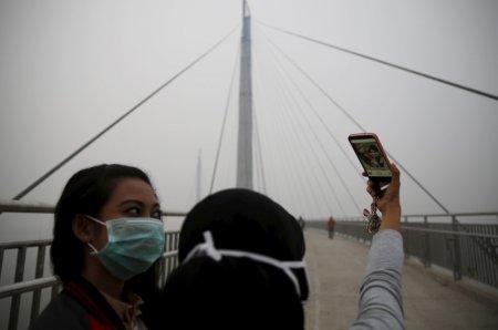 Girls take a selfie at the haze shrouded Batanghari River bridge in Jambi Indonesia Sumatra island