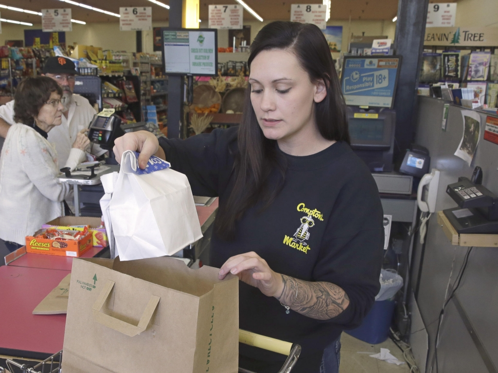 Checker Brittney Bounds bags groceries Tuesday in Sacramento Calif. Gov. Jerry Brown signed an equal pay measure that lets female employees challenge pay discrimination based on the wages a company pays to male employees who do similar work