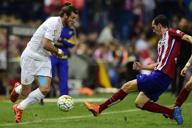 Gareth Bale vies with Diego Godin