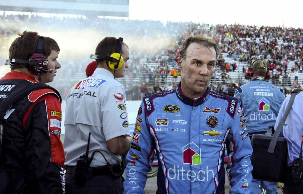 Smoke from Matt Kenseth's victory burnout hangs in the air behind Kevin Harvick as Harvick leaves the pit area after Sunday's NASCAR Sprint Cup race at New Hampshire Motor Speedway in Loudon N.H. Harvick who was in the lead ran out of gas near the end