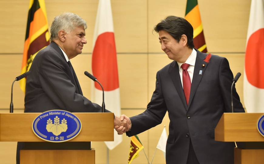 Sri Lankan Prime Minister Ranil Wickremesinghe and Prime Minister Shinzo Abe shake hands following a joint news conference in Abe's office in Tokyo on Tuesday. | AFP-JIJI