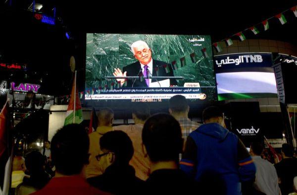 Palestinians watch a speech by Palestinian President Mahmoud