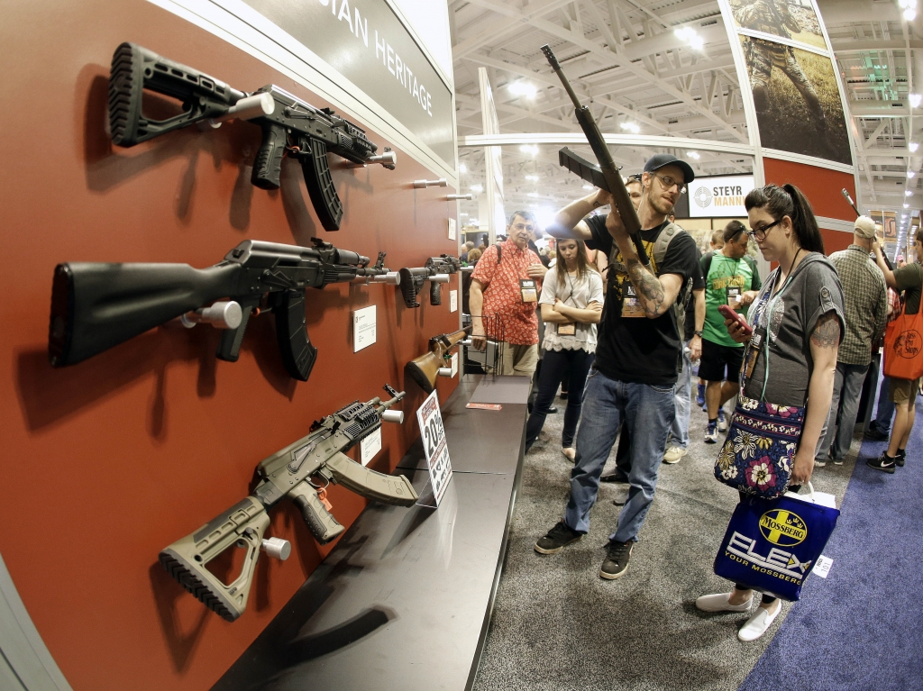 People examine rifles on display at the annual National Rifle Association convention in Nashville Tenn. in April.    Mark Humphrey       AP