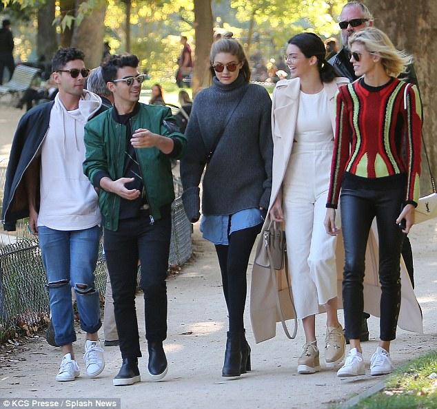 Stylish friends Gigi Hadid Joe Jonas Kendall Jenner and Devon Winsdor strolled throughMonceau park in Paris on Friday