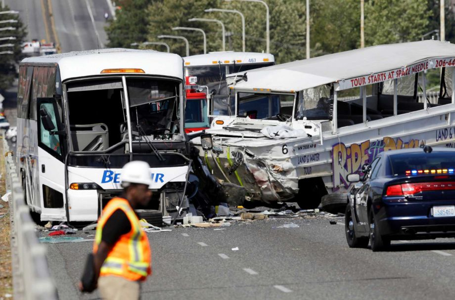 An emergency official stands near a charter bus left and a'Ride the Ducks amphibious tour bus following a fatal crash that killed five people Thursday Sept. 24 2015 in Seattle. The duck boat did not have an axle repair that was recommended for at