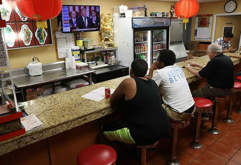Customers at a Chinese restaurant in Miami watch television Tuesday night as President Donald Trump delivers a speech to a joint session of the U.S. Congress