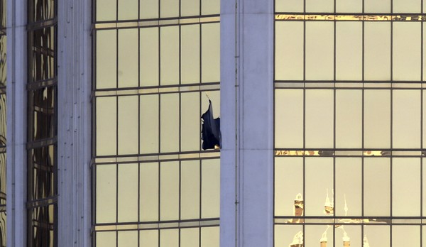 A broken window is seen at the Mandalay Bay resort and casino Monday Oct. 2 2017 on the Las Vegas Strip following a mass shooting at a music festival in Las Vegas. Authorities say Stephen Craig Paddock broke the window and began firing with a cache