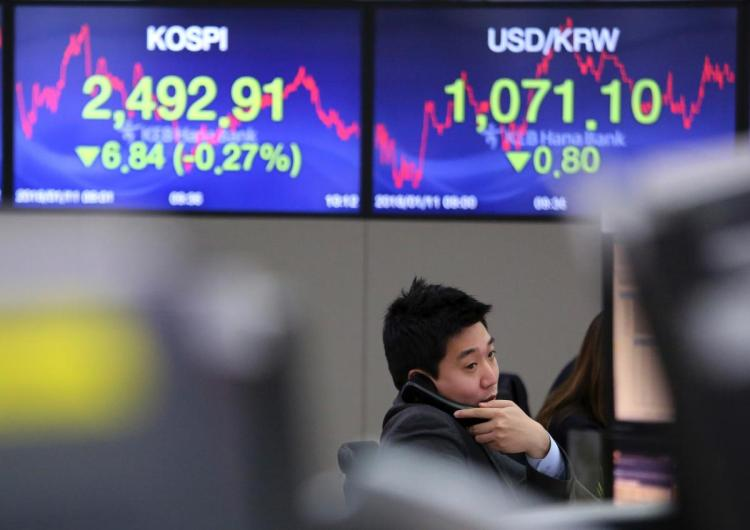 A currency trader talks on the phone at the foreign exchange dealing room of the KEB Hana Bank headquarters in Seoul South Korea Thursday Jan. 11 2018. Asian stock markets were lower on Thursday after Wall Street posted its first loss this year. Repor