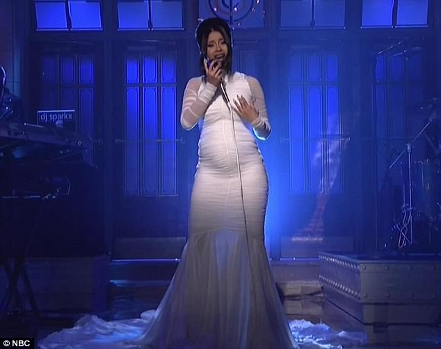 The big reveal Cardi made her announcement in style- by wearing a form-fitting dress on SNL