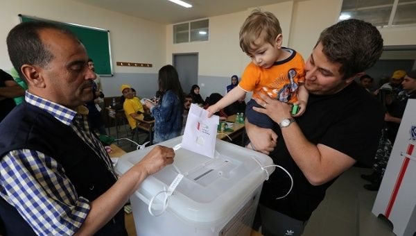 A child casts a ballot on behalf of his father during the parliamentary election in Tibnin Lebanon