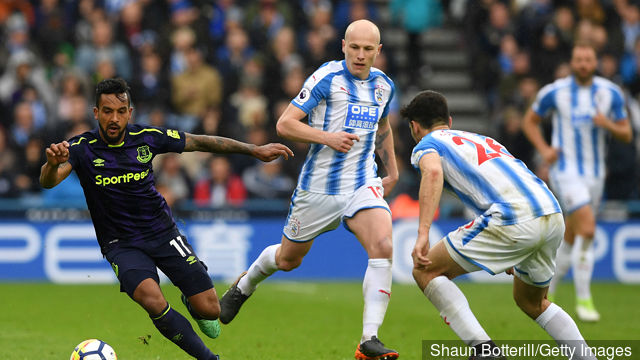 Aaron Mooy and Christopher Schindler of Huddersfield Town put pressure on Theo Walcott of Everton during the Premier League match between Huddersfield Town and Everton at John Smith's
