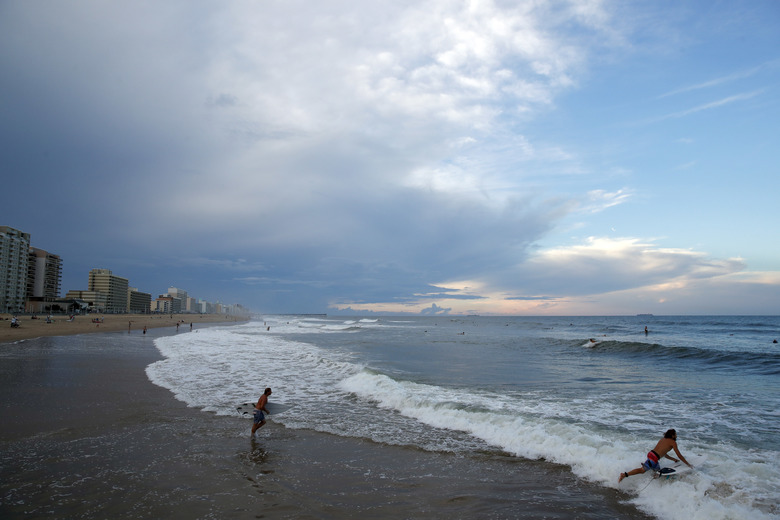 Surfers head to the waves Tuesday Sept. 11 2018 in Virginia Beach Va. before the arrival of Hurricane Florence