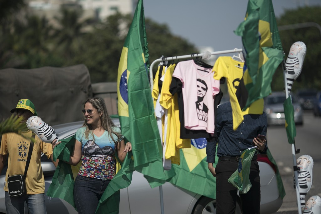 A supporter of presidential candidate Jair Bolsonaro of the Social Liberal Party buys a Brazilian flag being sold in front of the entrance of Bolsona